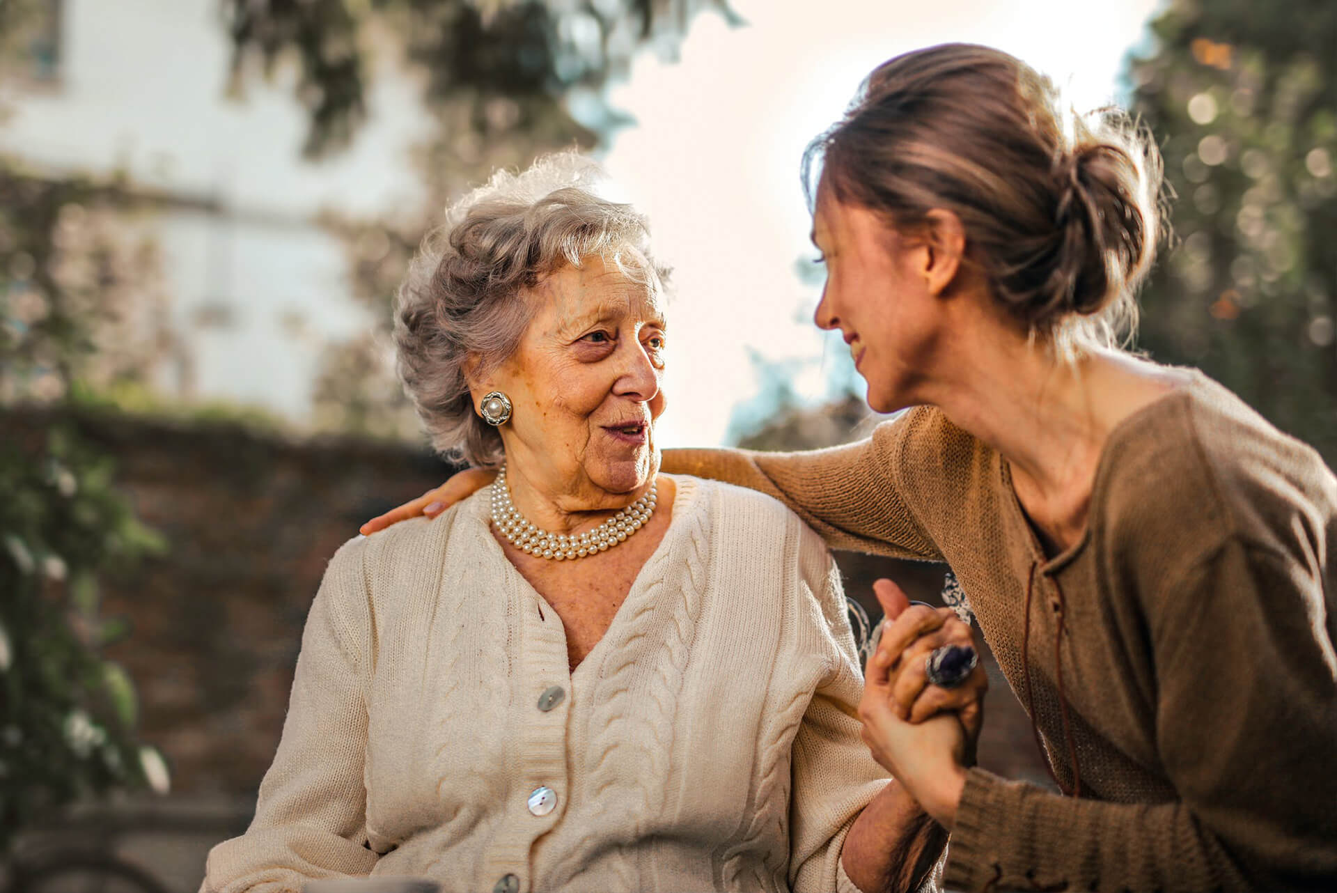 old women and daugther looking at each other in a garden